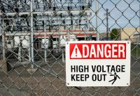 Danger high voltage keep out sign on fence in front of substation