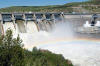 Water falling from hydro dam creating rainbow over larger body of water