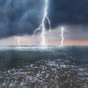 Three lightning strikes over ocean